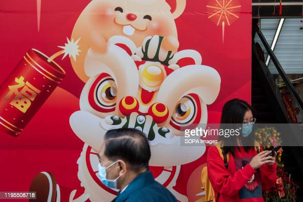 A woman stands next to a Chinese New Year sticker wall while wearing a sanitary mask after the first cases of coronavirus have been confirmed in Hong...