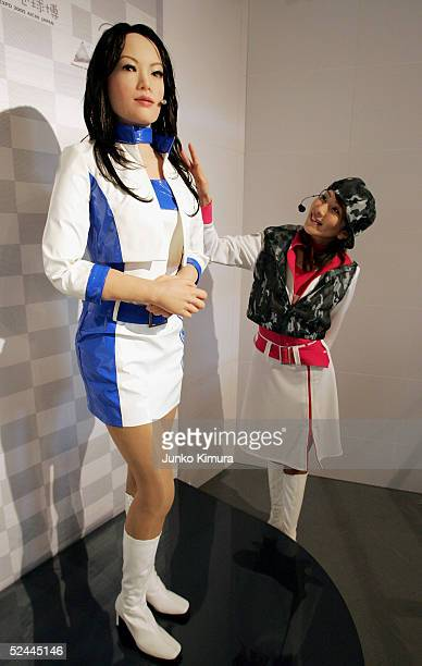 A woman stands next to a communication robot called 'Actroid' during the press day of the Aichi World Exposition 2005 on March 18 2005 in Nagakute...