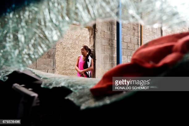 TOPSHOT A woman stands next to a damaged car at a supermarket parking bay in Valencia Carabobo State on May 5 the day after antigovernment protesters...