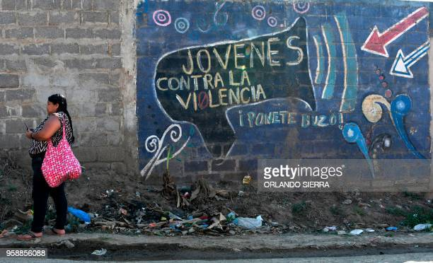A woman stands next to a graffiti reading Youths Against Violence in the poor neighbourhood of Nueva Capital on the outskirts of Tegucigalpa on May...