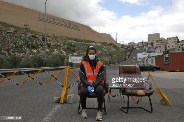 TOPSHOT A woman stands next to a makeshift checkpoint part of a community safety initiative in the Druze village of Majdal Shams in the Israelannexed...