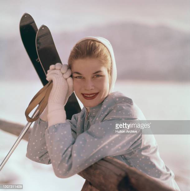 A woman stands next to a pair of skis wearing light blue spotted ski jacket white hooded thermal shirt and white wool gloves circa 1950