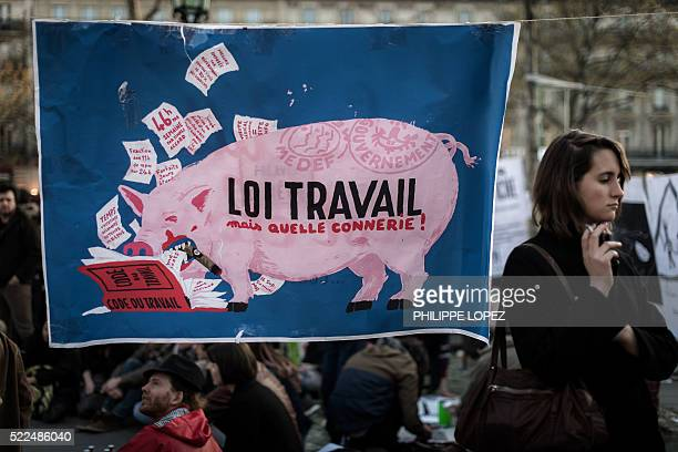 A woman stands next to a sign reading 'Labour law what bullshit' at the Place de la Republique in Paris during the 'Nuit Debout' movement to protest...