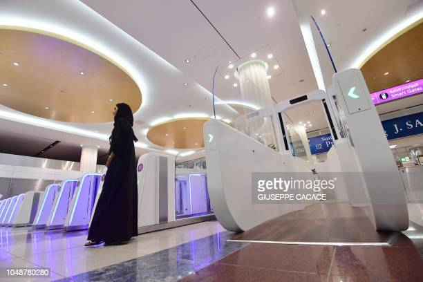 A woman stands next to a smart tunnel at Dubai International Airport's terminal 3 in United Arab Emirates on October 10 2018 The Smart tunnel using...