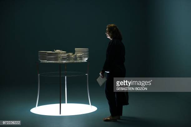 """Woman stands next to an artwork by Barbara Bloom titled """"The Tip of the Iceberg"""" on June 12, 2018 during the preview day of Art Basel, world's..."""