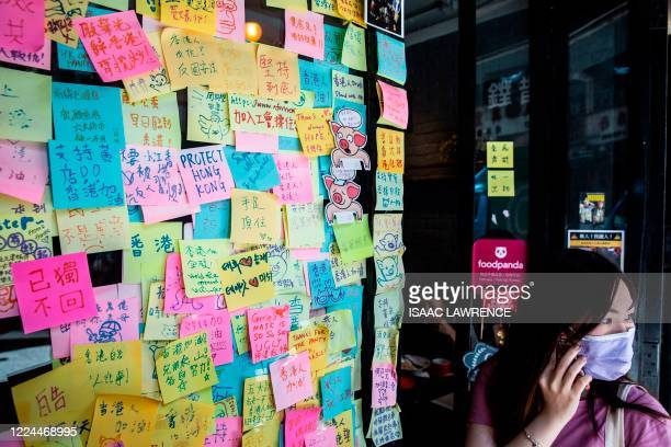 Woman stands next to layers of notes on a Lennon Wall with messages of support for the pro-democracy protests outside a restaurant in Hong Kong on...