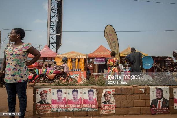 Woman stands next to Samantha Nassolo and Bakaluba Mukasa election posters in Kampala. Uganda's elections are expected to take place early next year.