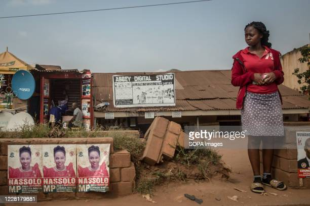 Woman stands next to Samantha Nassolo election posters in Kampala. Uganda's elections are expected to take place early next year.