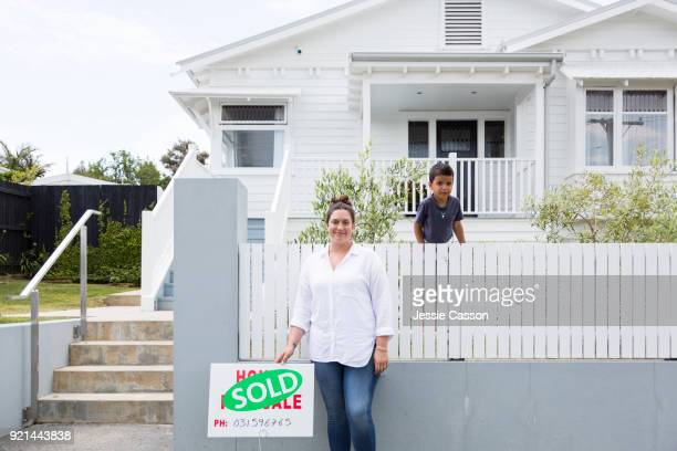 Woman stands next to Sold sign in front of white traditional villa while boy stands on fence behind