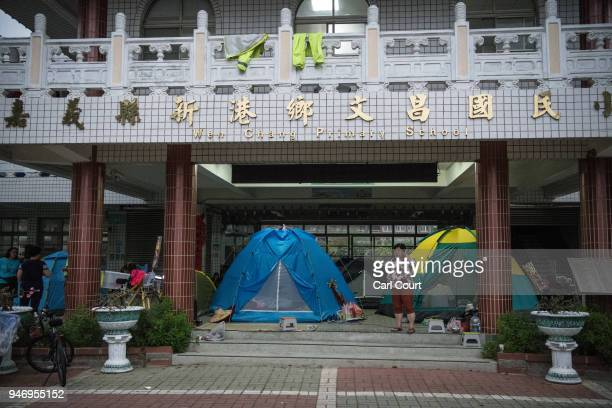 A woman stands next to tents pitched in a school near Xingang Fengtian Temple that has been allocated for pilgrims who are following the statue of...