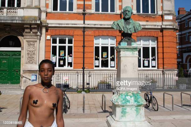 A woman stands next to the bronze bust to Sir Henry Tate in Windrush Square Brixton during a Black Lives Mater marchThere is a campaign to recover...