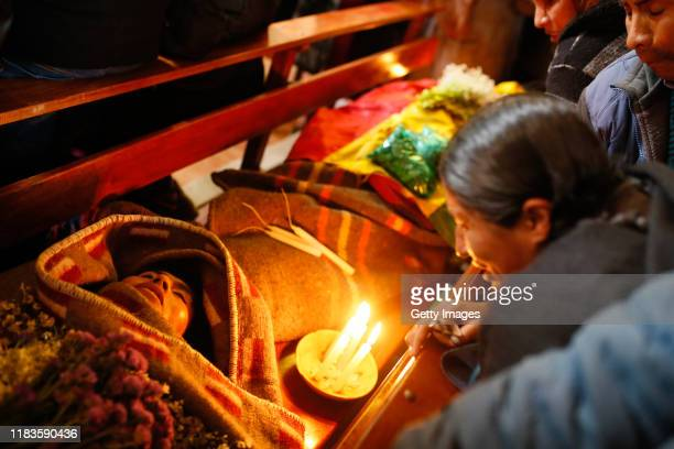 A woman stands next to the corpse of a man during the funeral of people killed yesterday during clashes between supporters of Evo Morales and...