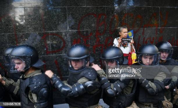TOPSHOT A woman stands next to the Ukrainian riot police in front of the Prosecutor General's Office in Kiev to prevent attacks of activists of the...