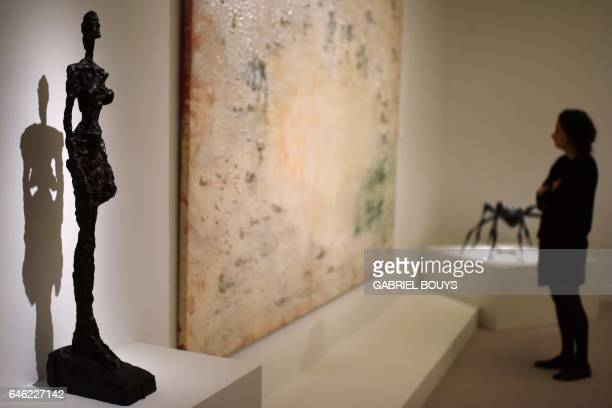 A woman stands next to 'Woman from Venice' a sculpture by Alberto Giacometti during the exhibition 'From Zurbaran to Rothko Collection Alicia...