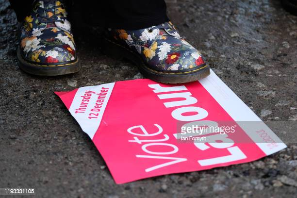 A woman stands on a Labour placard as supporters gather for a stump speech by Labour leader Jeremy Corbyn at the Sporting Lodge Inn on December 11...