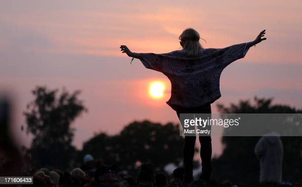 Woman stands on a rock at the stone circle as people gather for sunset at the Glastonbury Festival of Contemporary Performing Arts site at Worthy...
