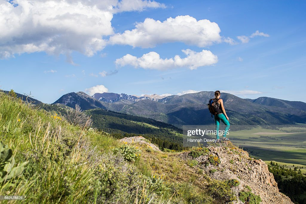 Woman stands on a rock looking out in the Rocky Mountains of Montana : Stock Photo