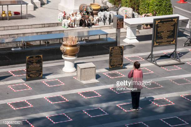 Woman stands on a social distancing square while praying in front of a shrine near Ratchadamri Road. The Thai government has applied social...