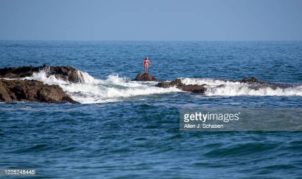 Woman stands on a submerged rock, taking in the scenic view at sunset off the coast of south Laguna Beach as SoCal beaches reopen Monday after being...