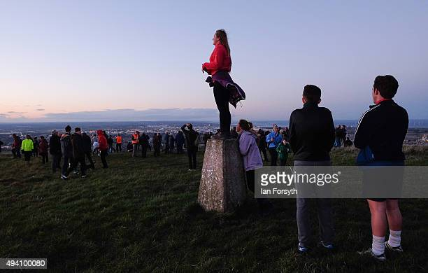 A woman stands on a trig point during a torchlit procession on the top of the Eston Hills on October 24 2015 in Eston Cleveland The event was...