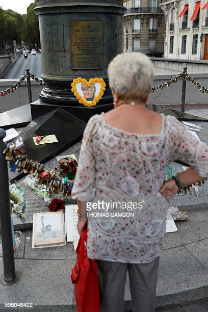 A woman stands on August 31 2016 at The flame of Liberty replica monument became an unofficial memorial for late Britain's Princess Diana at the Alma...
