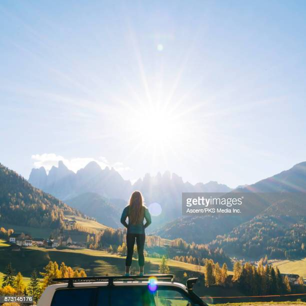 woman stands on car rooftop looking at mountains in the distance - pedal pushers stock pictures, royalty-free photos & images