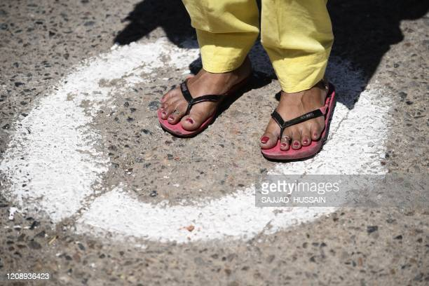 A woman stands on circle marked on the ground to maintain distancing at a food distribution for those in need organised by the Disciples of...