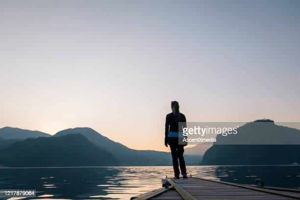 woman stands on edge of dock over lake and watches sunrise over mountains and forest - clear sky stock pictures, royalty-free photos & images