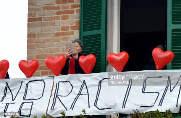 A woman stands on her balcony where she put red balloons with the victims' names and a banner reading no to racism during an antiracism demonstration...