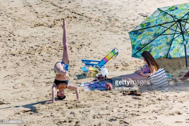 A woman stands on her head on the beach while a friend records her on Memorial Day weekend on May 22 in Virginia Beach VA This is the first day of...