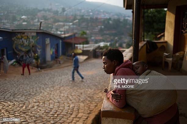 A woman stands on her porch at a suburb set on a hill overlooking Kigali on March 13 2014 Twenty years after the genocide of Rwanda's Tutsi minority...