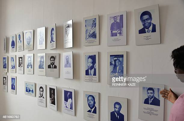 A woman stands on January 13 2015 next to photos of figures of Cameroon's history exhibited at the National Museum of Cameroon in Yaounde The museum...