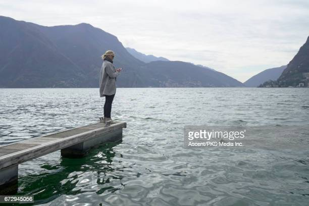 woman stands on lake pier, sends text - jetty stock pictures, royalty-free photos & images