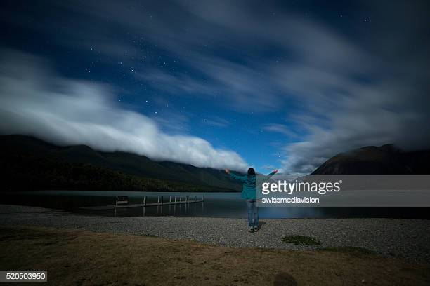 Woman stands on lake shore at night, arms outstretched