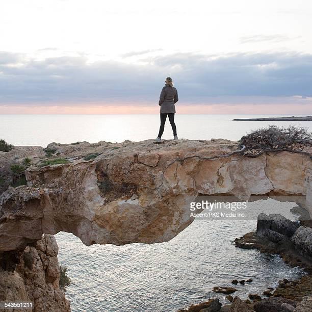 woman stands on natural bridge, looks to sea - natuurlijke brug stockfoto's en -beelden