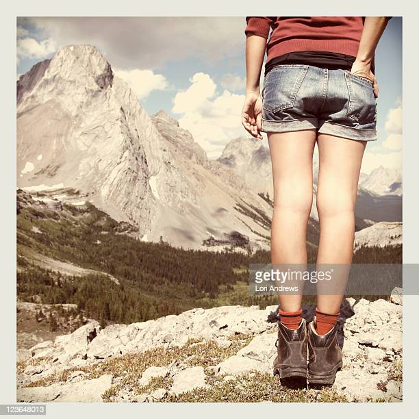 Woman stands on ridge over looking mountains