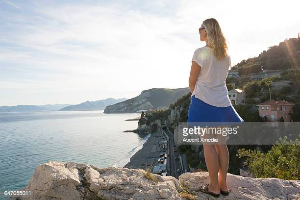 Woman stands on rock bluff, looks out to coastline