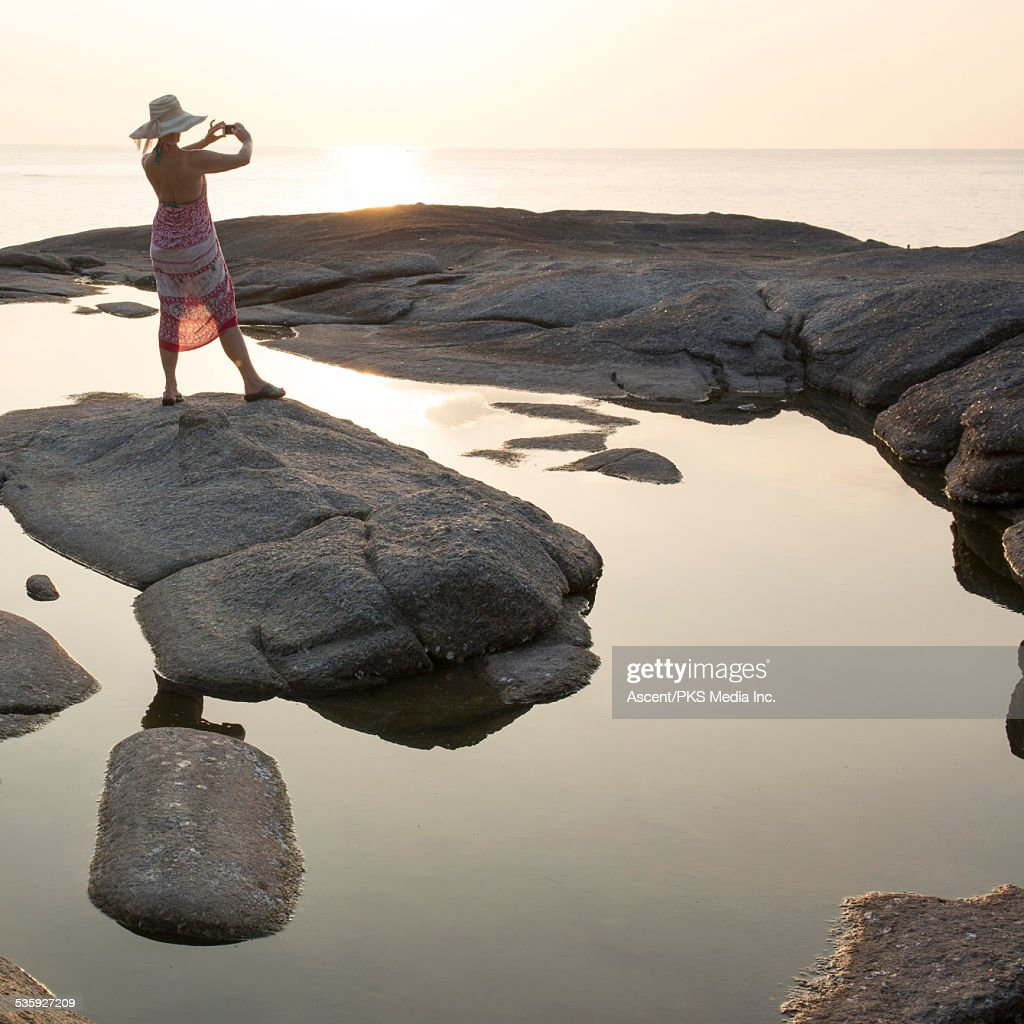 Woman stands on rock island, takes pic of sea, sun : Stock Photo