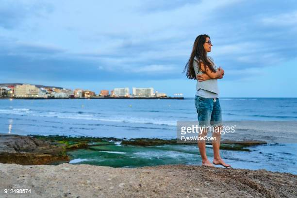 Woman stands on rocks at the coastline on January 18 2018 in El Medano Tenerife Spain Model released