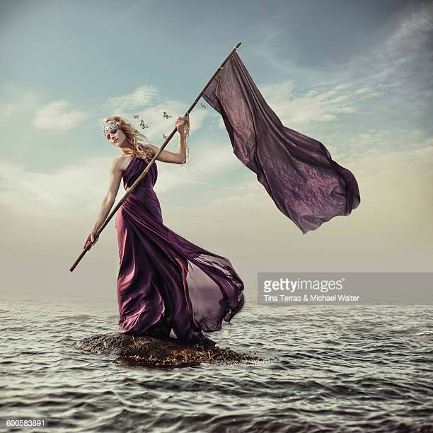 woman stands on rocks in the sea - evening gown stock pictures, royalty-free photos & images
