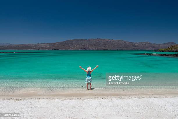 Woman stands on sandy beach, lifts arms overhead