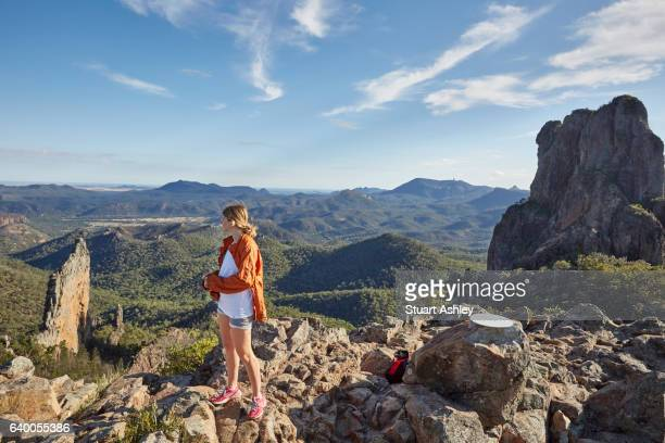 Woman stands on scenic lookout over Warrumbungle National Park