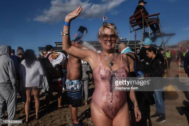 A woman stands on the beach after participating in the annual Polar Bear Plunge on New Year's Day in Coney Island on January 1 2019 in the Brooklyn...