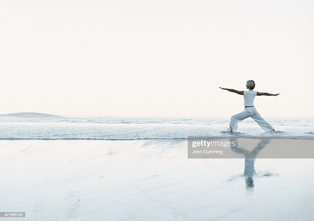 Woman Stands on the Beach at the Water's Edge, Exercising : Stock Photo