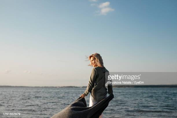 a woman stands on the beach in the setting sun - one mature woman only stock pictures, royalty-free photos & images