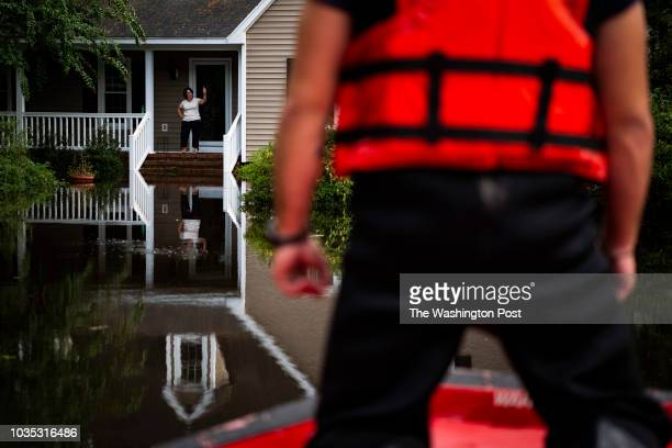 A woman stands on the porch at a home as members of a punt team with the United States Coast Guard preform search and rescue through flood waters in...