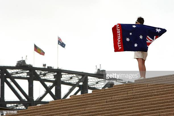 A woman stands on the steps of the Sydney Opera House looking out to the Aboriginal and Australian flags flying on the Sydney Harbour Bridge on the...