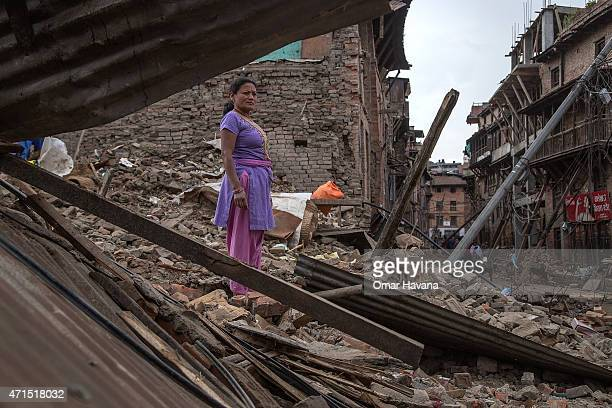 Woman stands on top of debris from her collapsed house on April 29, 2015 in Bhaktapur, Nepal. A major 7.8 earthquake hit Kathmandu mid-day on...