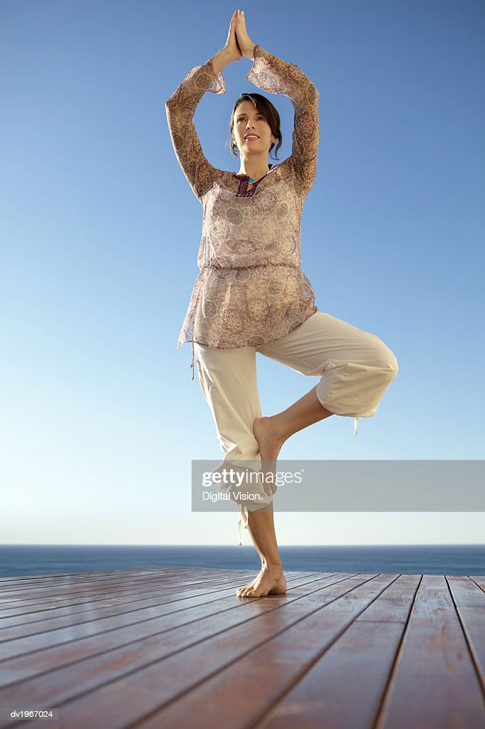 Woman Stands Outdoors in a Yoga Position, On One Leg With Her Arms Above Her Head : Stock Photo