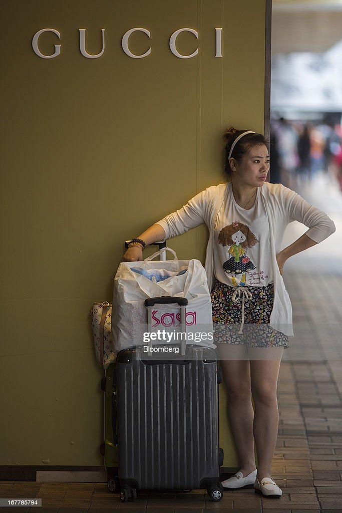 A woman stands outside a Gucci store, a luxury unit of PPR SA, with a suitcase in the Tsim Sha Tsui area of Hong Kong, China, on Tuesday, April 30, 2013. Financial Secretary John Tsang on Feb. 27 projected annual growth of 1.5 percent to 3.5 percent this year following 2012's 1.4 percent, the weakest rate since 2009 as Europe's sovereign debt crisis sapped global demand. Photographer: Lam Yik Fei/Bloomberg via Getty Images